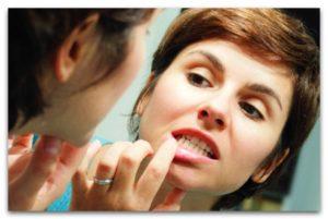 девушка у зеркала проверяет зубную полость