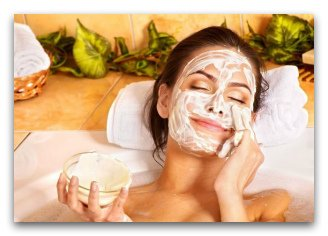 Женщина намазывает лицо кремом