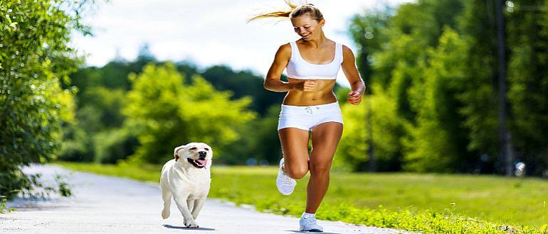 Спортивная девушка бежит с собакой
