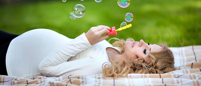 Беременная женщина пускает мыльные пузыри