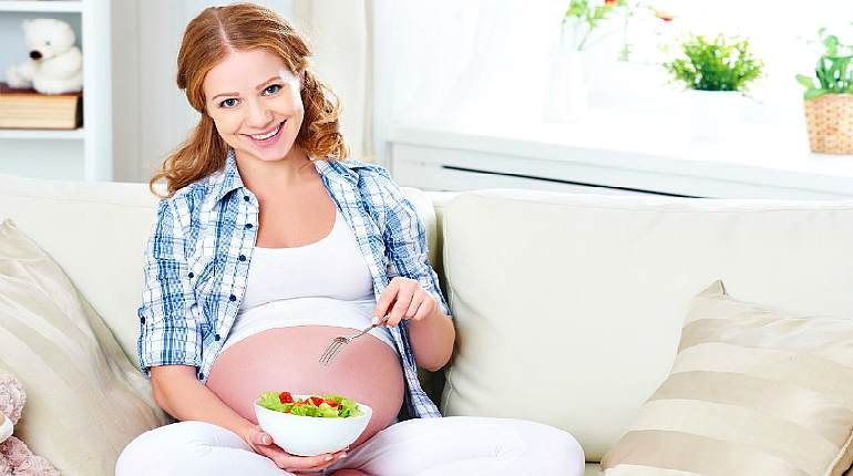 Беременная девушка ест салат из овощей